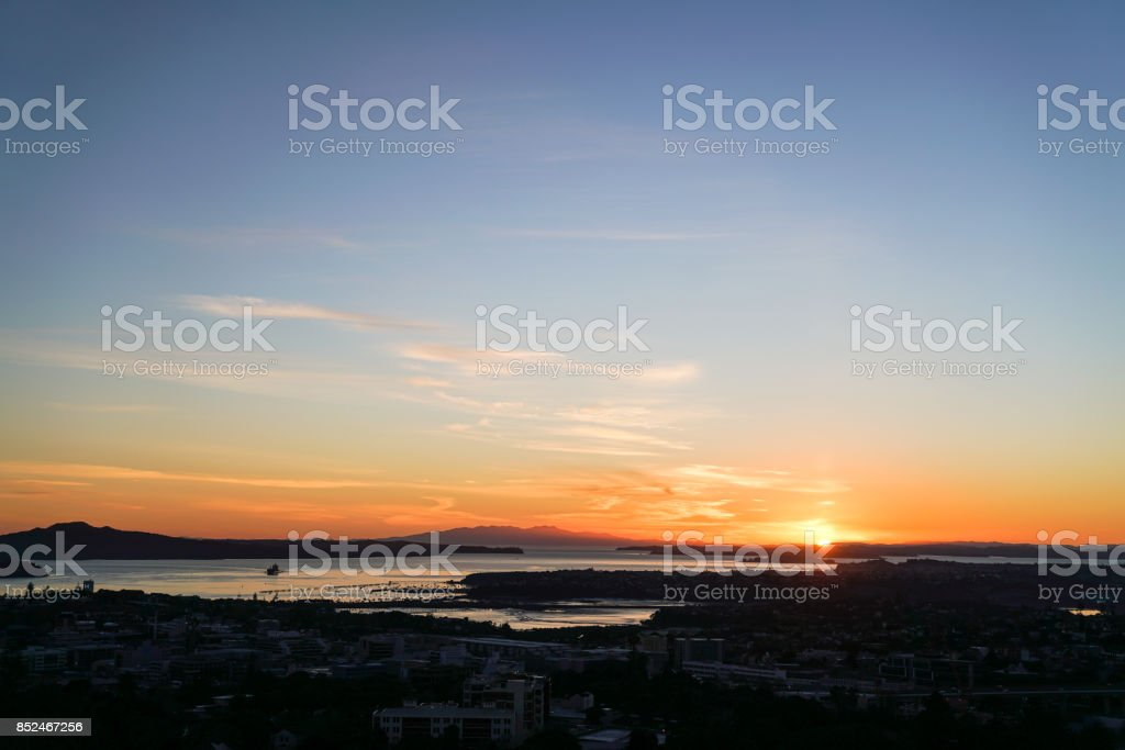 Auckland city and Rangitoto Island in silhouette at sunrise from top Mount Eden, New Zealand. stock photo