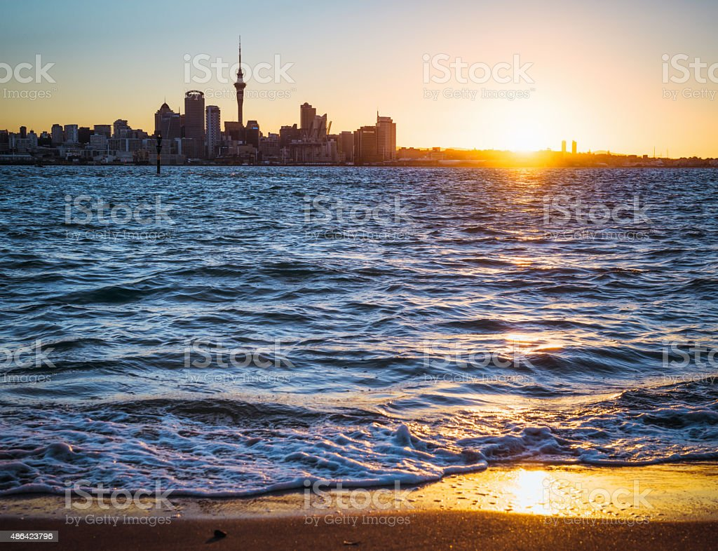 Auckland skyline at sunset from Devonport beach stock photo