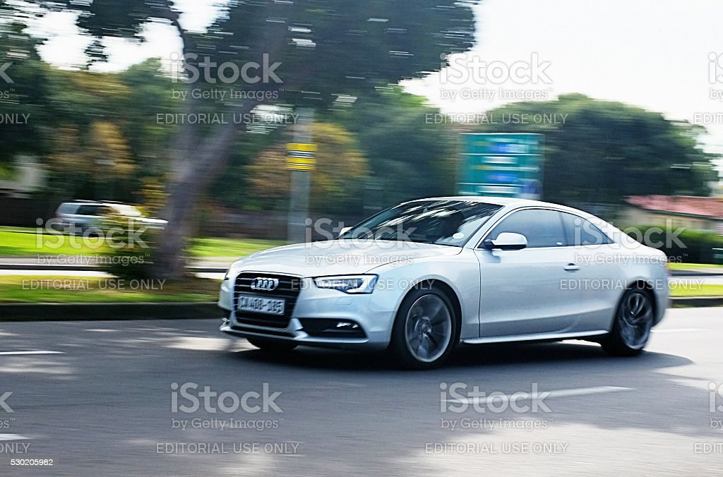 Audi A4 travelling on suburban main road. stock photo