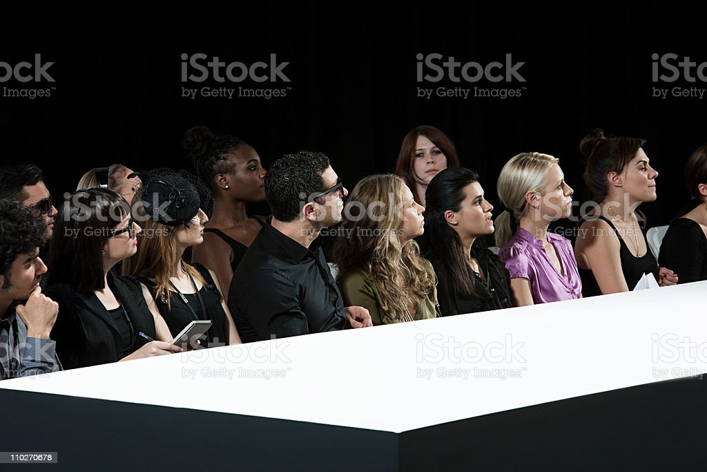 Audience at fashion show watching empty catwalk stock photo