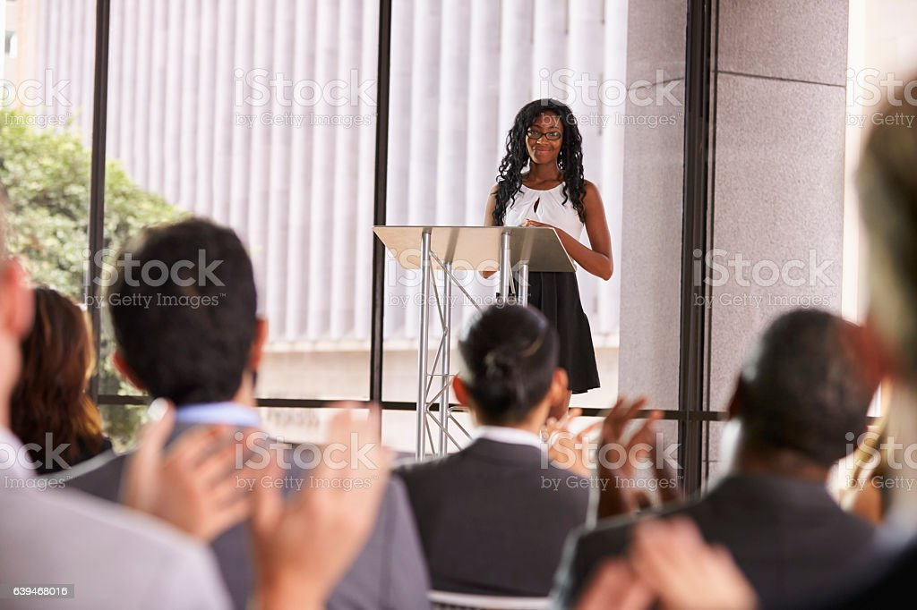 Audience at seminar applauding young black woman at lectern stock photo