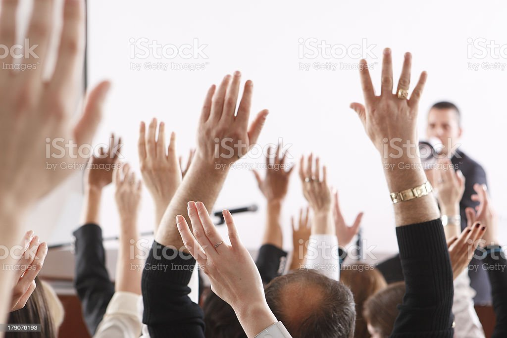Audience raising hands in seminar or class room stock photo