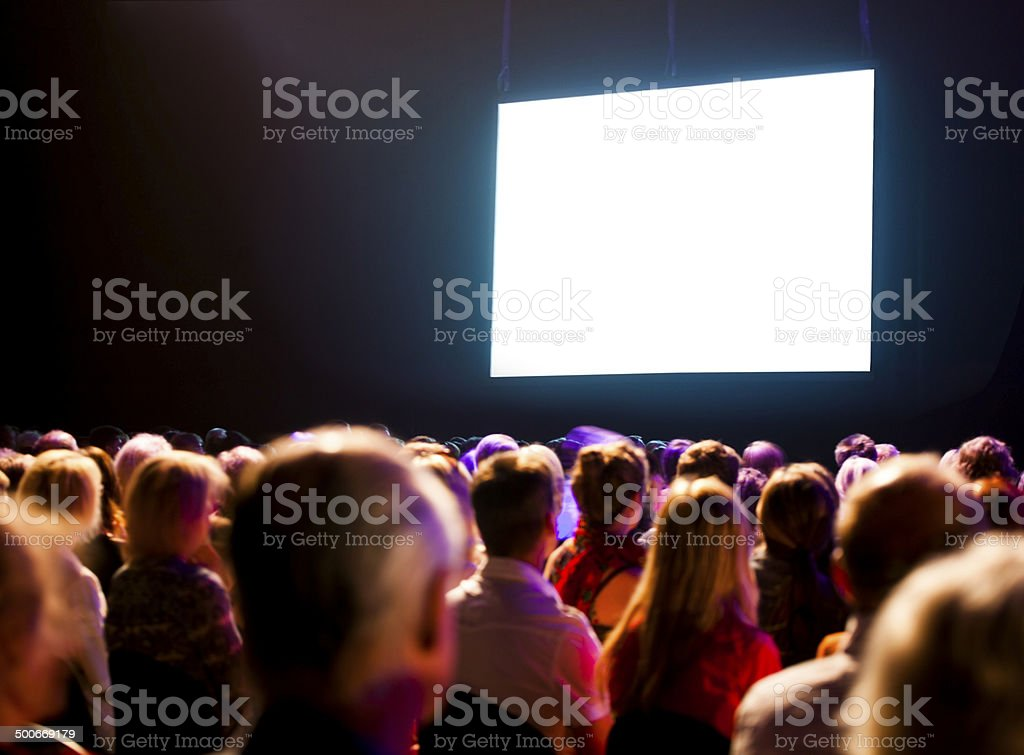 Audience watching a bright blank screen stock photo