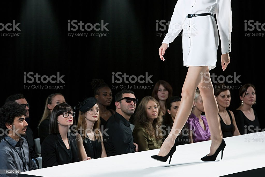 Audience watching model on catwalk at fashion show, low section stock photo