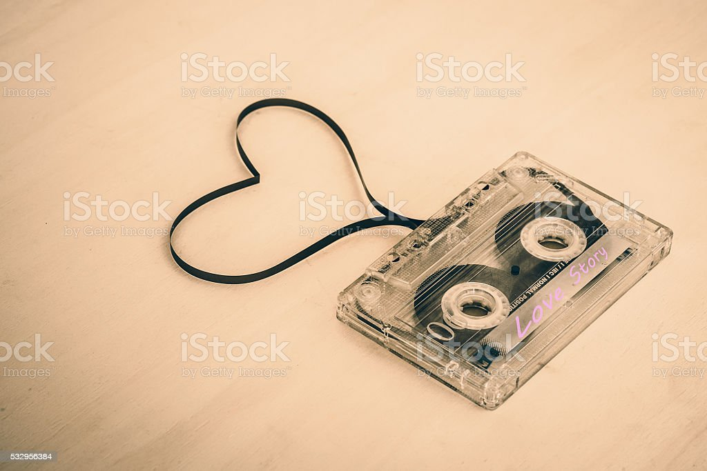 Audio cassette tape on wooden backgound. Film shaping heart stock photo