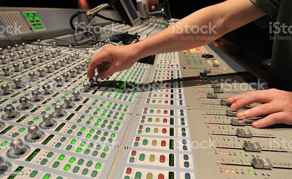 Audio engineer operating mixing console royalty-free stock photo