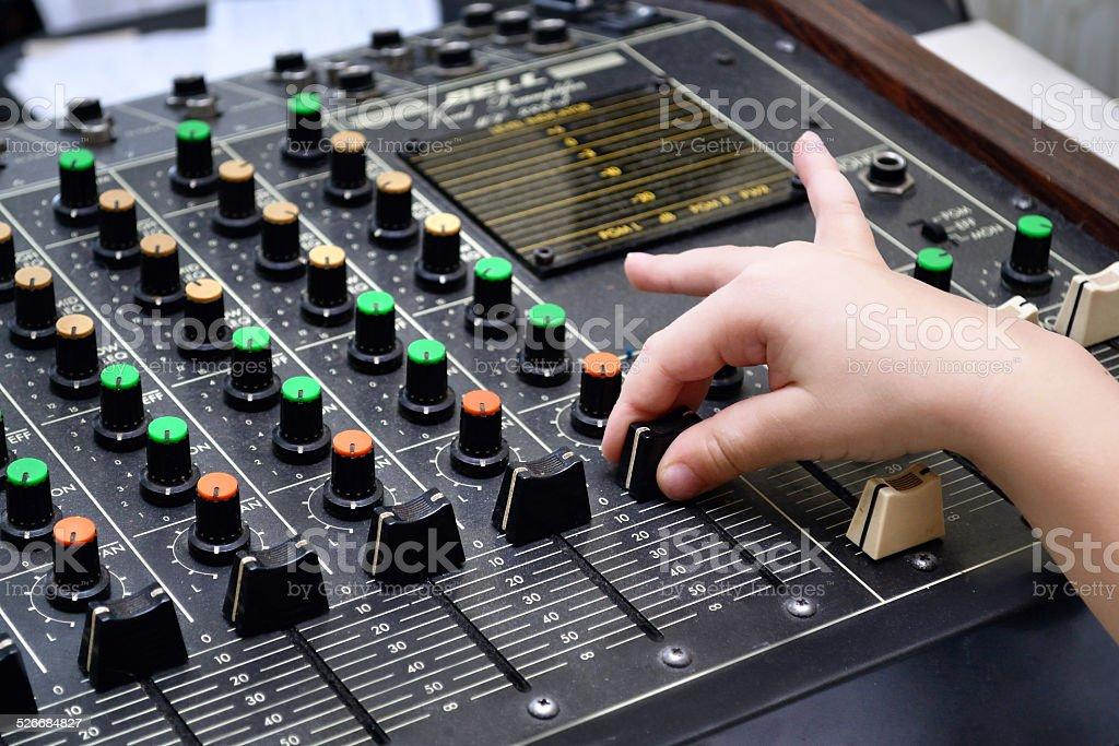Audio sound mixer and child`s hand black and white stock photo