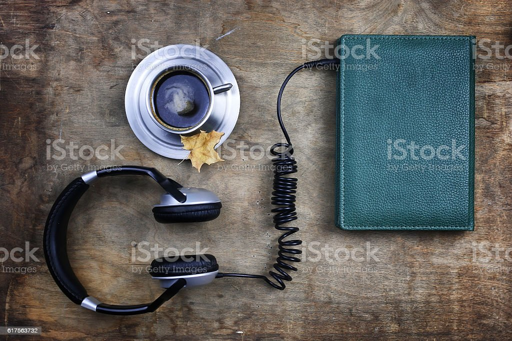 audiobook headphones and book on wooden table stock photo