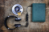 audiobook headphones and book on wooden table