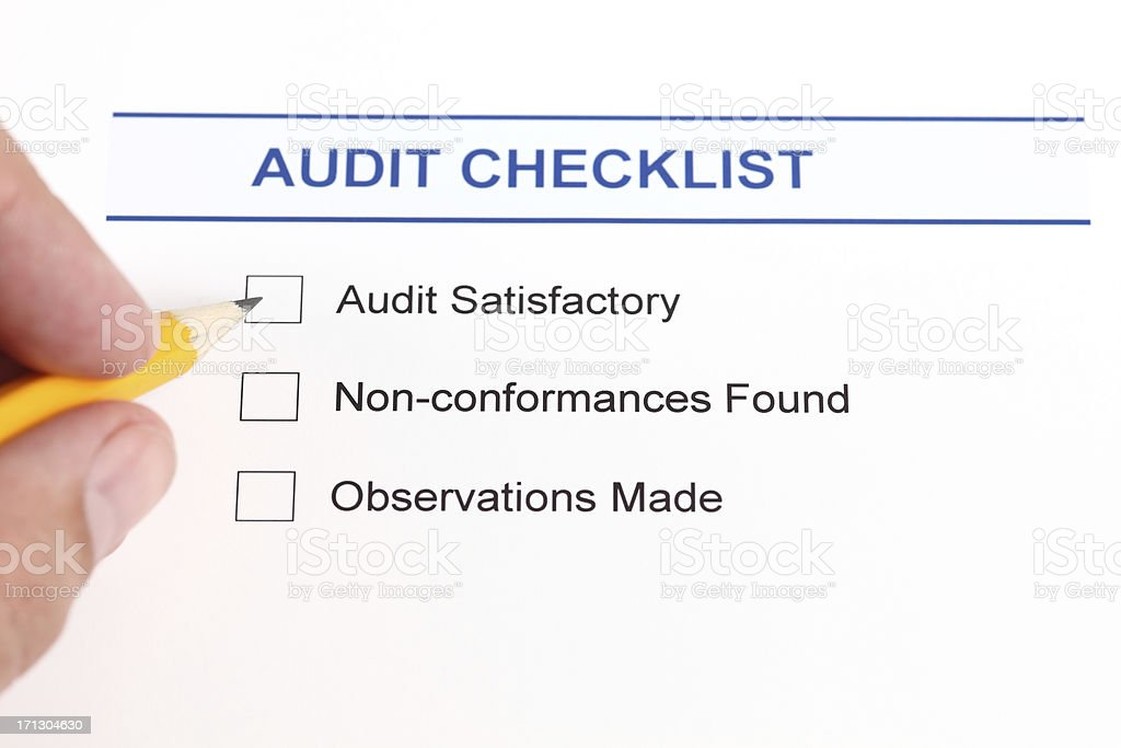 Audit checklist and human hand with pencil. stock photo
