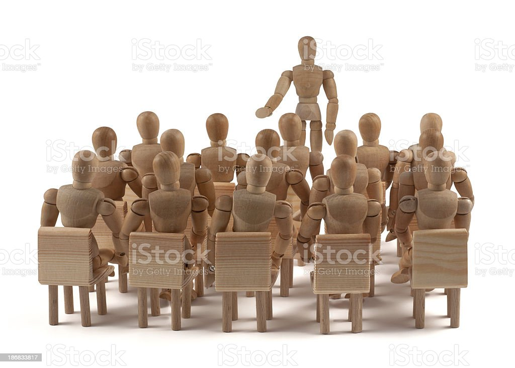 Auditorium of wooden mannequins and speaker royalty-free stock photo
