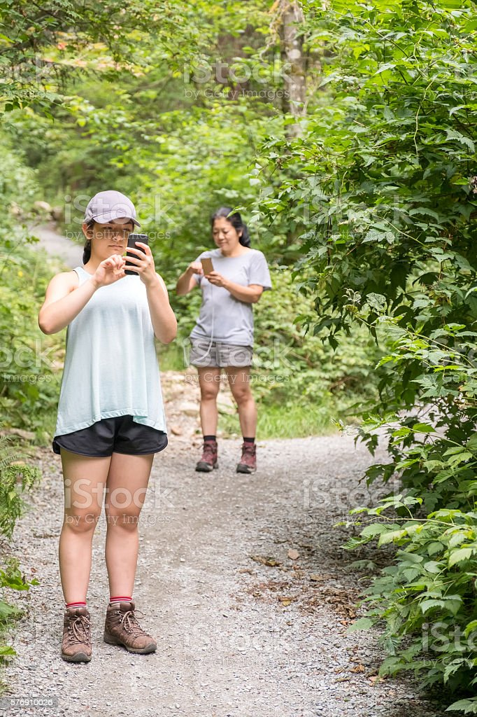 Augmented Reality Mobile Game, Woman, Teenaged  Hikers Playing in Forest stock photo