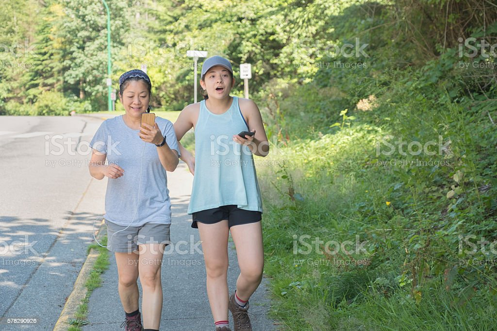 Augmented Reality Mobile Phone Gamers, Young Women Running with Smartphones stock photo