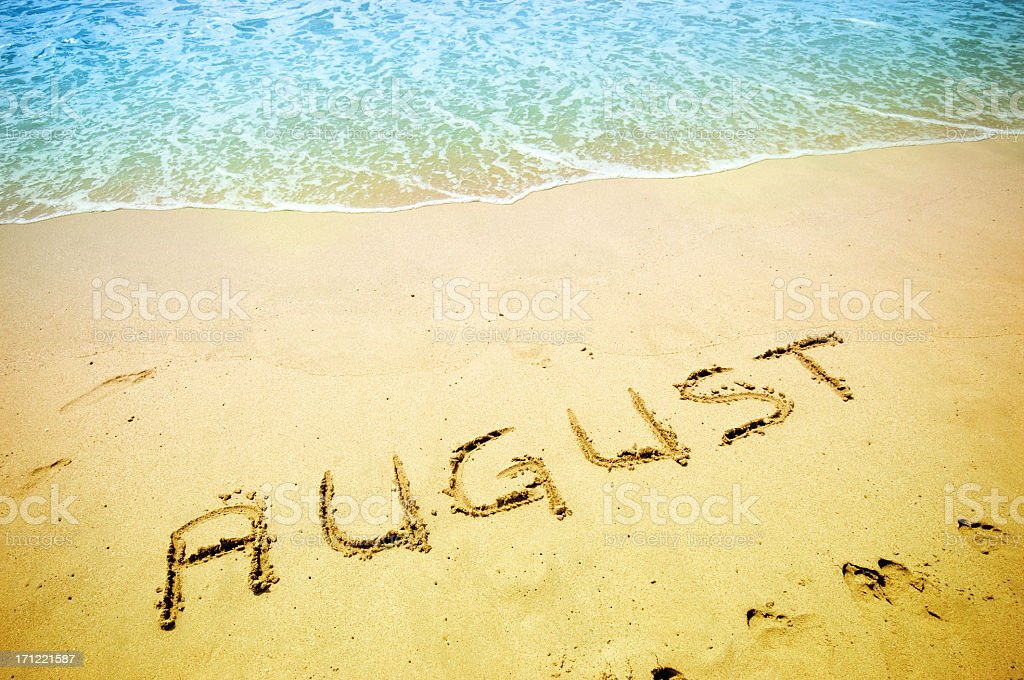 August handwritten in the sandy shoreline stock photo