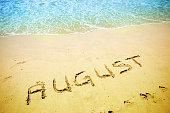 August handwritten in the sandy shoreline