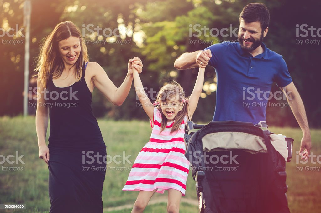 Aunt and uncle having fun with their niece in nature stock photo