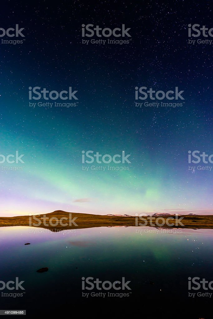 Aurora and glittering stars reflecting in tranquil mountain lake Iceland stock photo