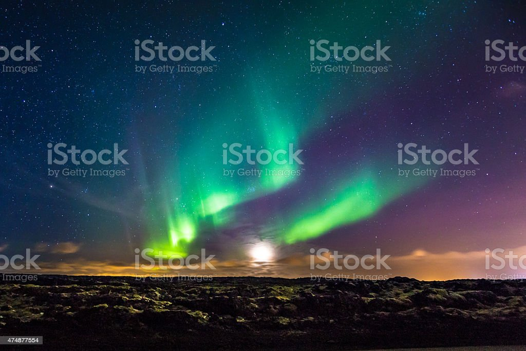Aurora Borealis and Moon setting above lava fields in Iceland stock photo