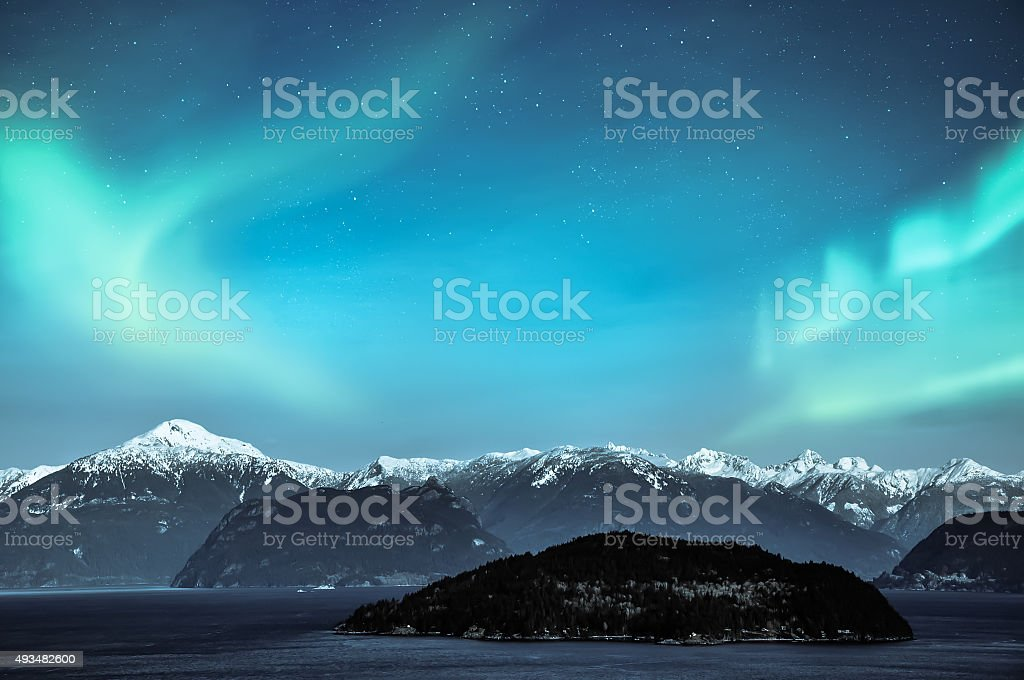 aurora borealis northern lights over snow mountains stock photo