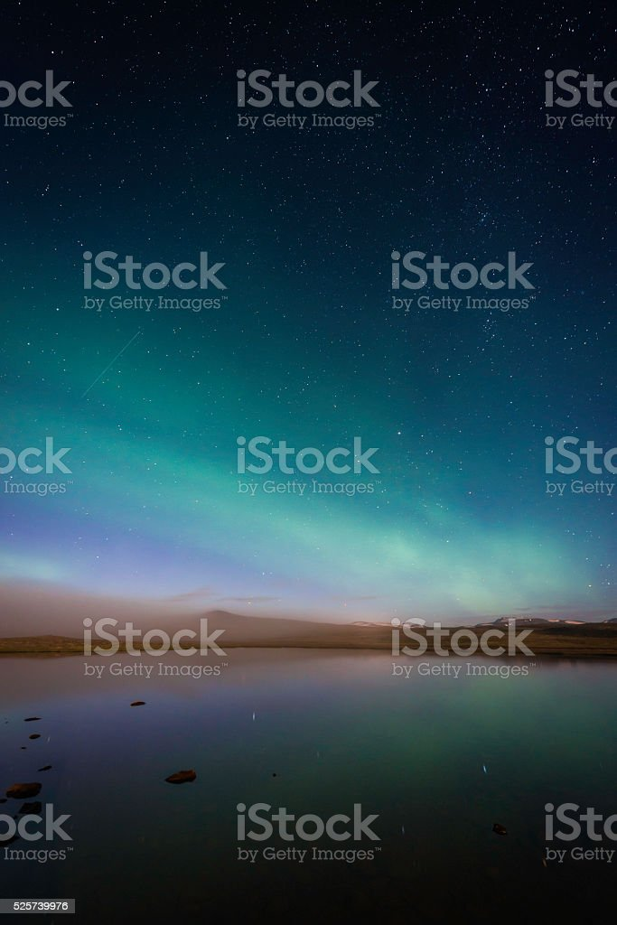 Aurora Borealis Northern Lights starry night reflecting mountain lake Iceland stock photo