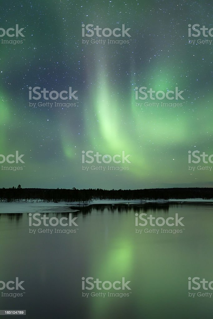 Aurora borealis over a lake in winter, Finnish Lapland royalty-free stock photo