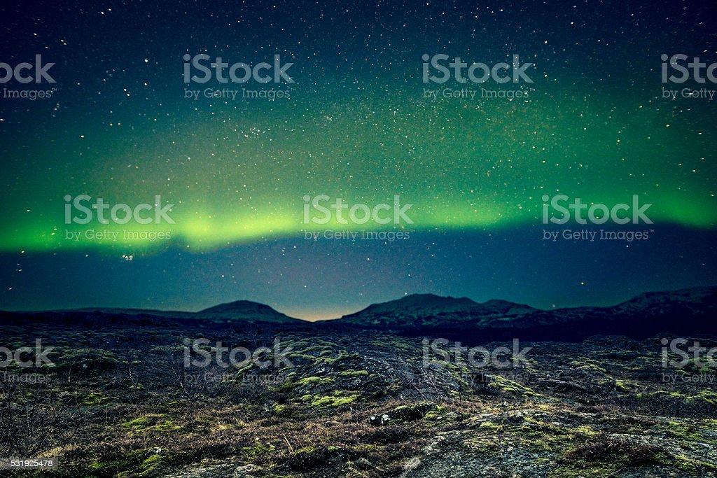 Aurora Borealis over distant mountains stock photo