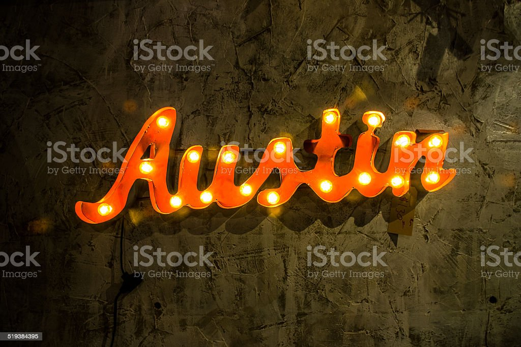 Austin Light Up Metal Sign Hanging on Textured Wall stock photo