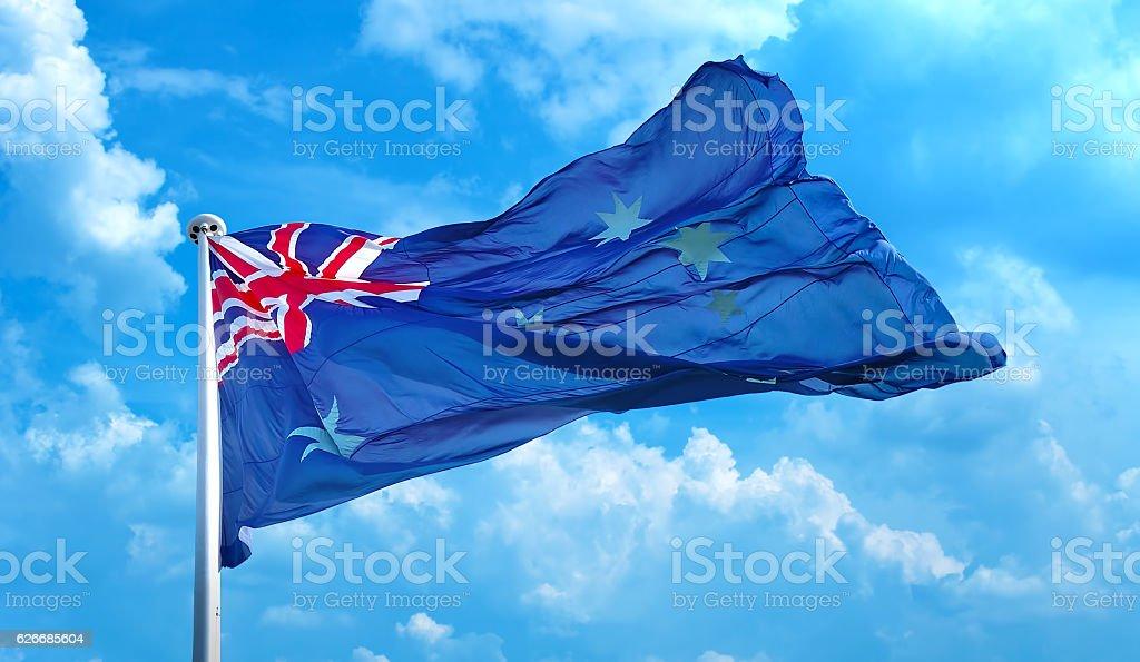 Australia flag waving in blue cloudy sky stock photo