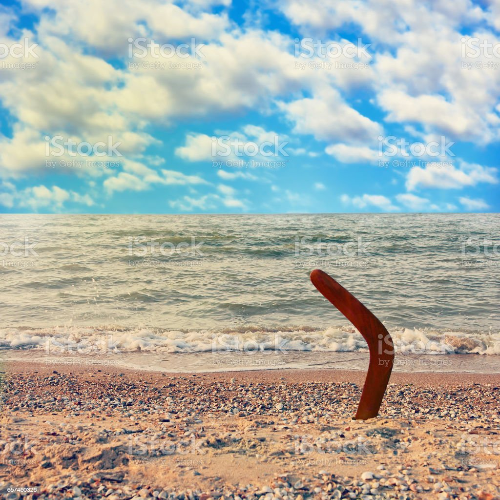 Australian Boomerang on tropical beach against sea wave and blue sky. stock photo