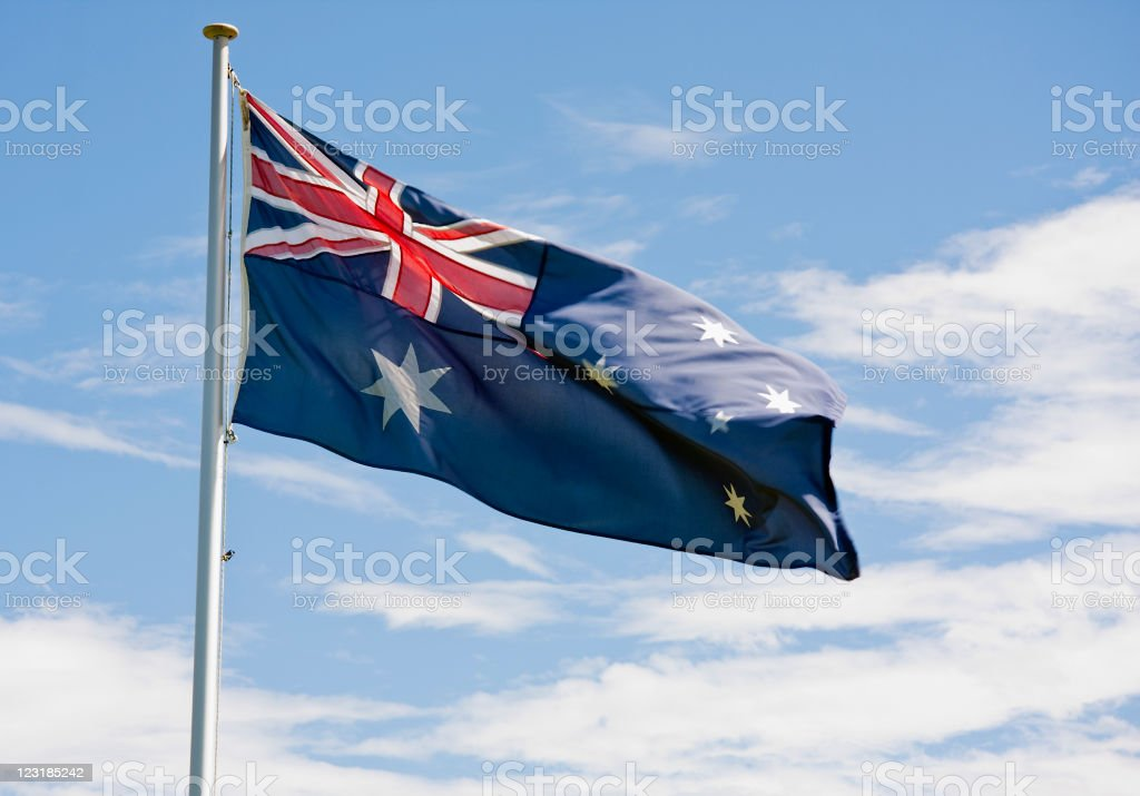 Australian Flag fluttering in the wind against a blue sky stock photo