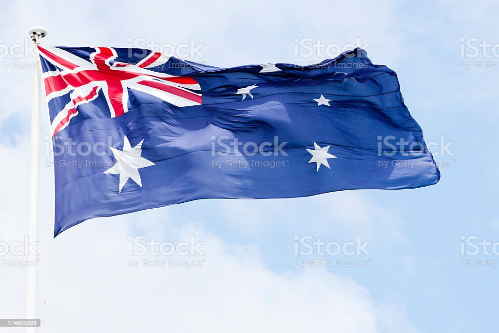 Australian flag in the wind against sky, copy space stock photo