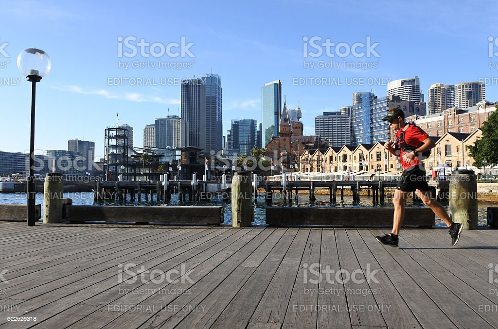Australian man runs on Circular Quay Wharf in Sydney, Australia stock photo