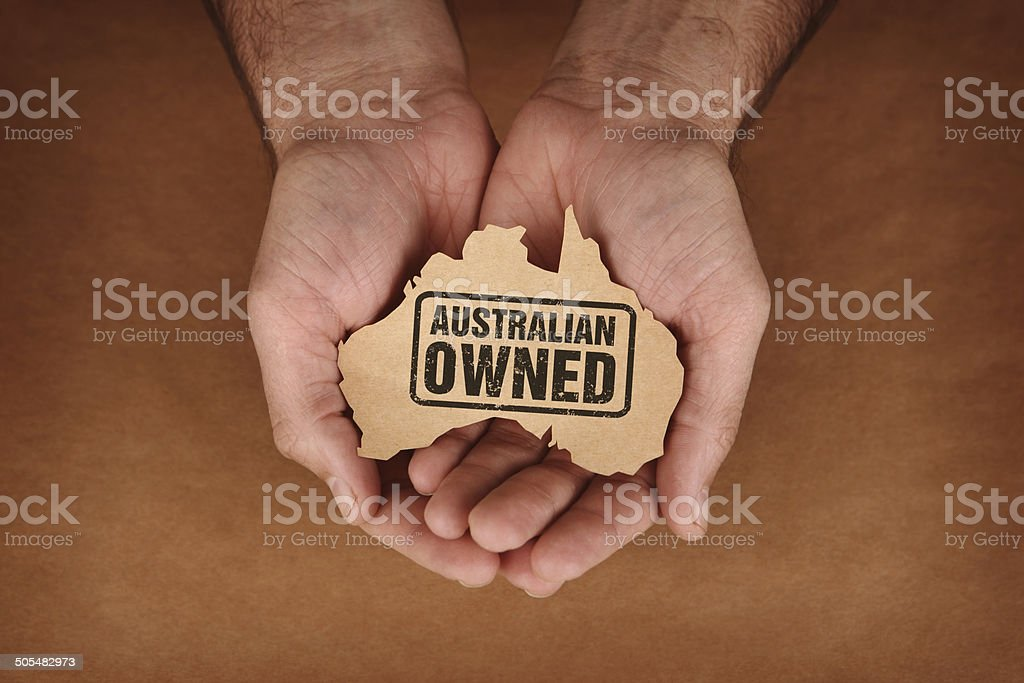 Australian Owned Stamped on Brown Paper Australia Shape in Hands stock photo