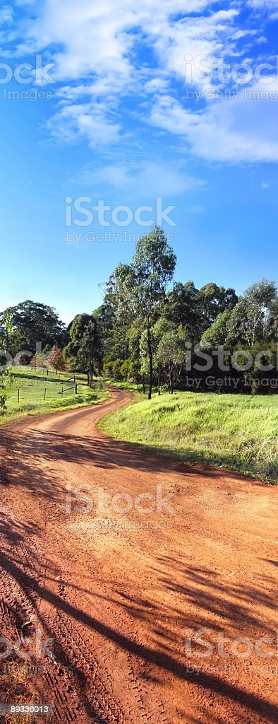 Australian rural Landscape with red sandy road and green field stock photo