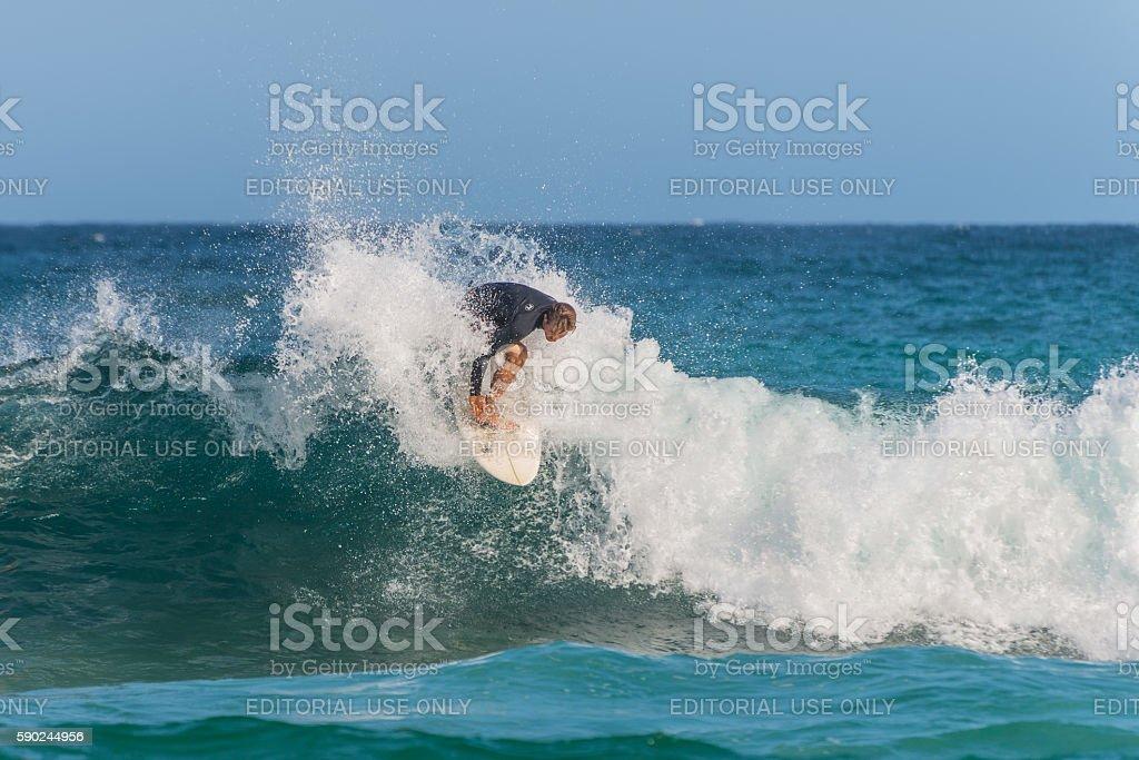 Australian surfer catching a wave stock photo
