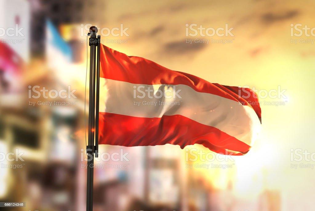 Austria Flag Against City Blurred Background At Sunrise Backlight stock photo