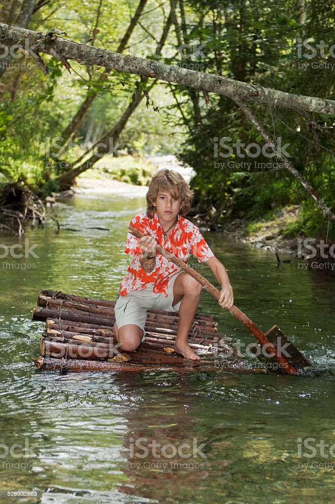 Austria, Salzburger Land, Boy on timber raft, paddling stock photo