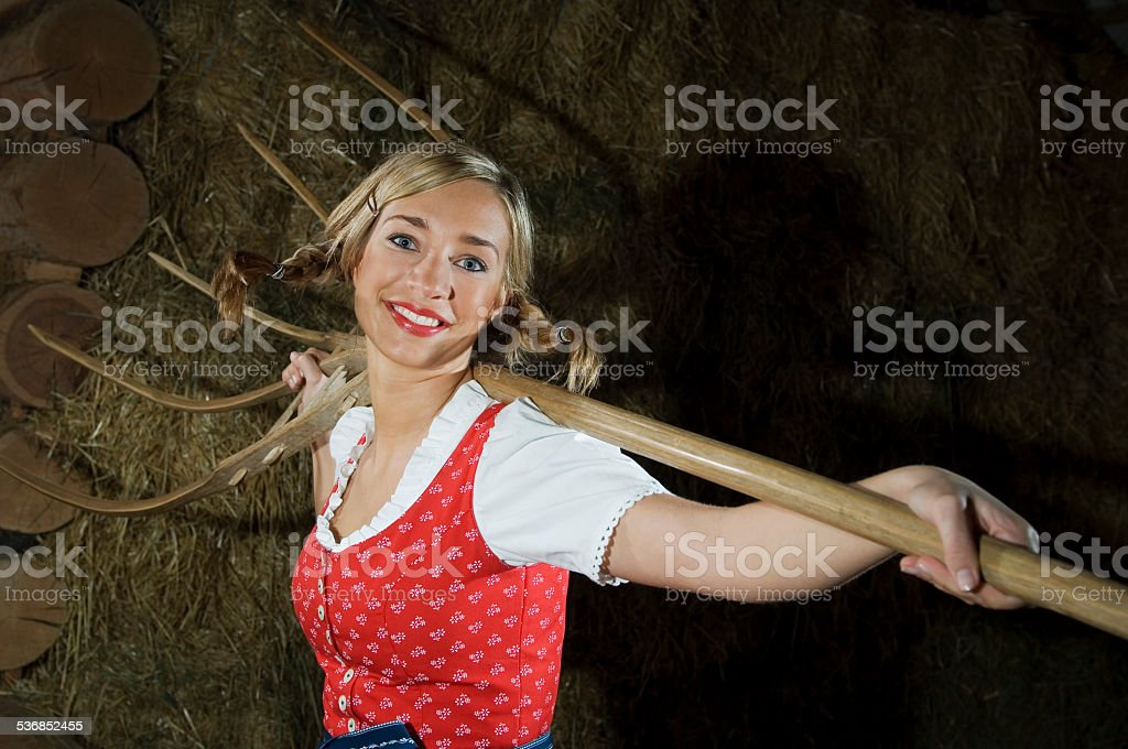 Austria, Salzburger Land, Young woman holding hay fork , portrait stock photo