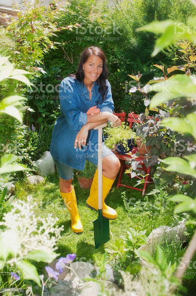 Austria, Salzburger Land, Young woman in garden, leaning against spade stock photo