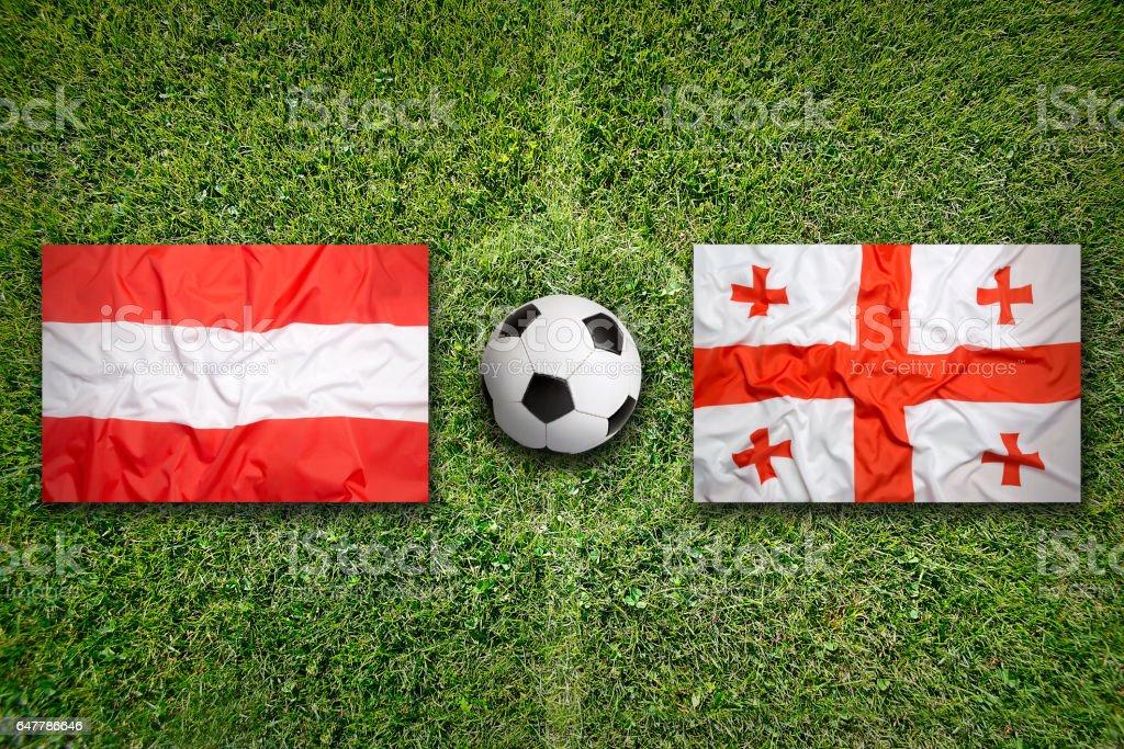 Austria vs. Georgia flags on soccer field stock photo