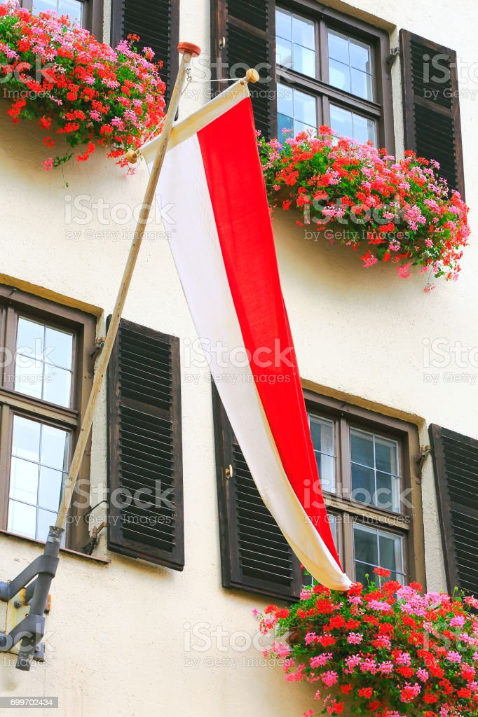 Austrian flag and detail facade of Innsbruck old town, Cityscape panorama of Tirol capital,  Austria stock photo