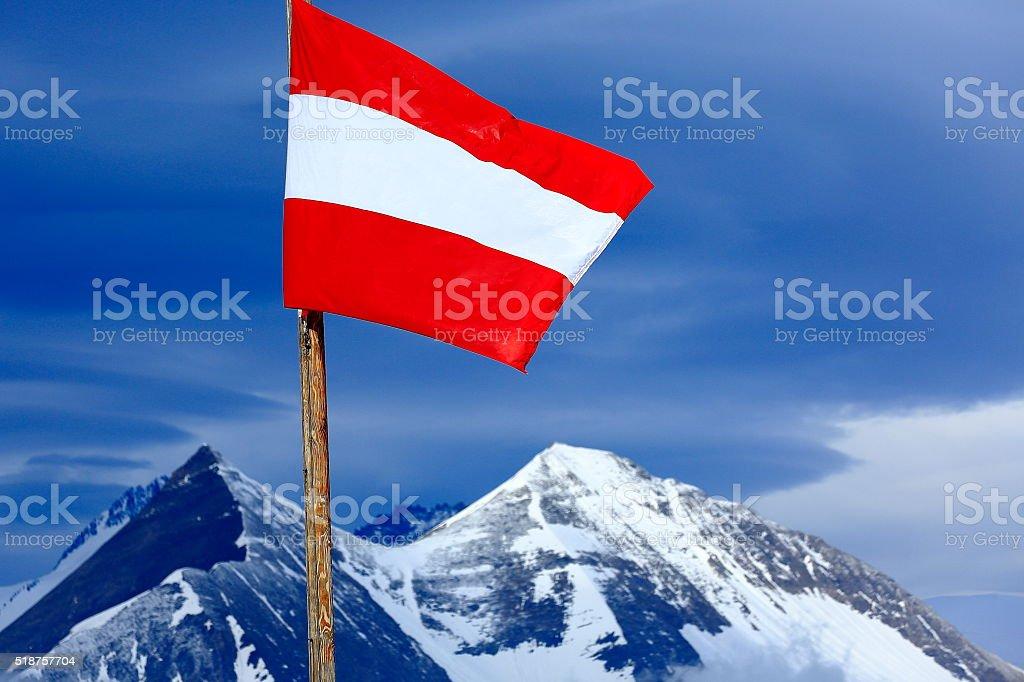 Austrian flag, Hohe Tauern alpine summit, dramatic sunset - Grossglockner stock photo