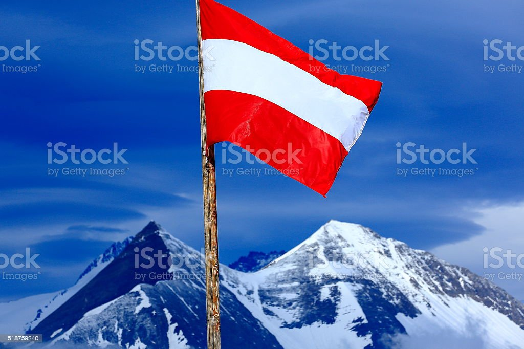 Austrian flag, Hohe Tauern alpine summit, dramatic sunset - Grossglockner stock photo