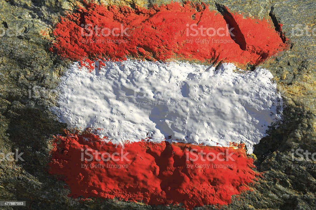 Austrian flag symbol painted on a rock in a trail stock photo