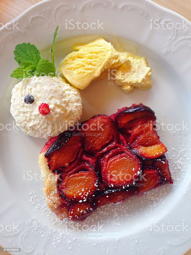Austrian Plum sheet Cake with Vanilla icecream and whipped cream stock photo