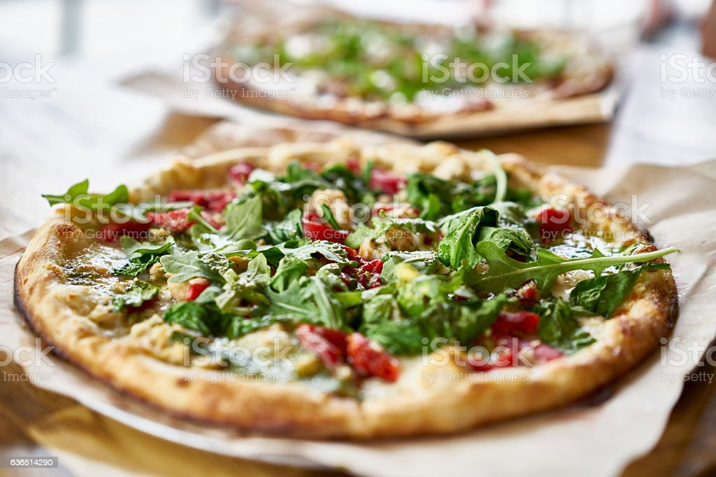 authentic gourmet pizza with fresh arugula, pesto and chicken stock photo
