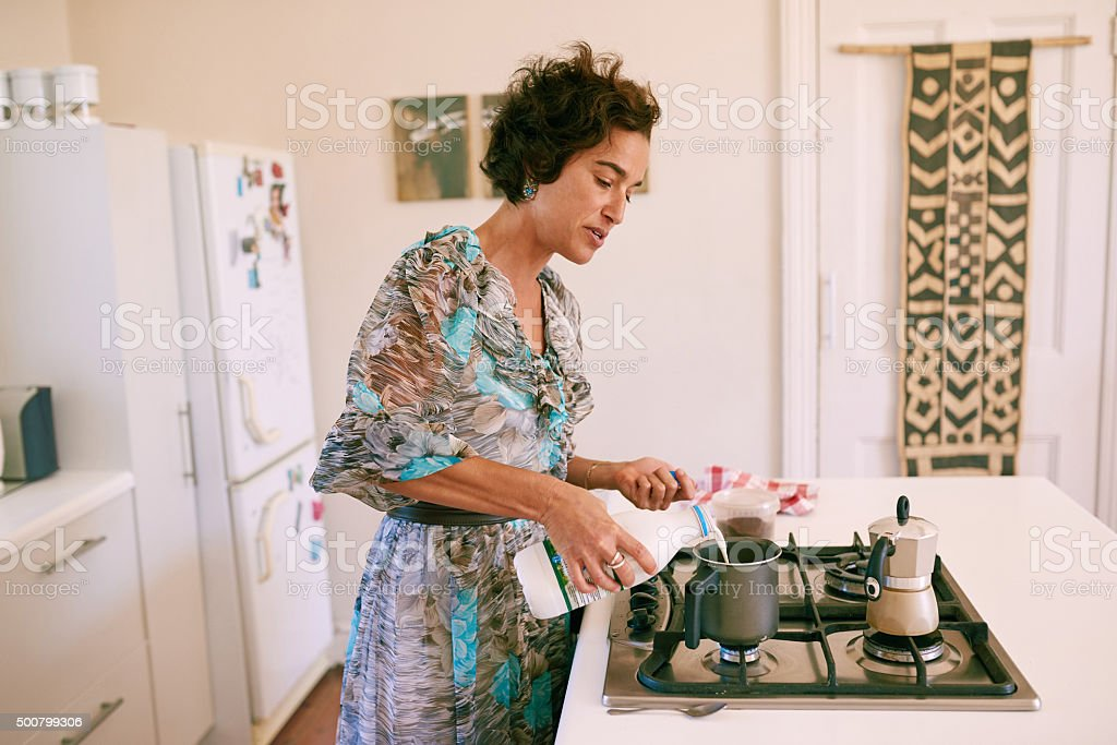Authentic image of a mature woman preparing milk for coffee stock photo