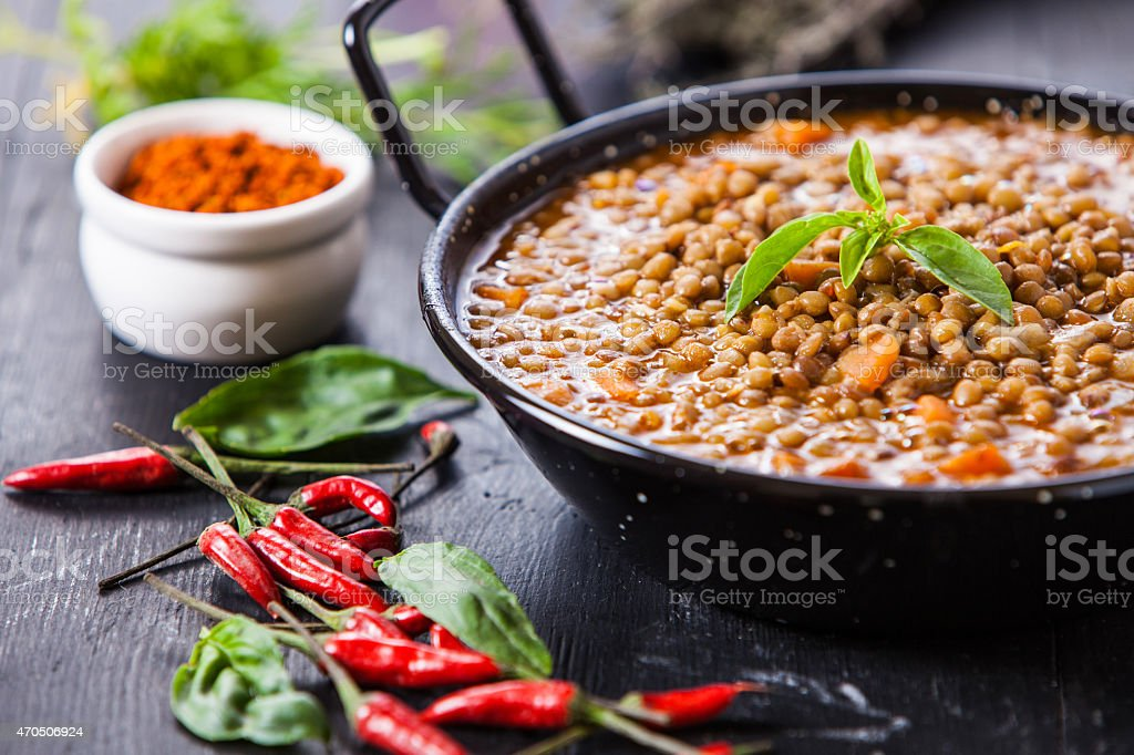 Authentic Indian dish surrounded by mini hot peppers stock photo