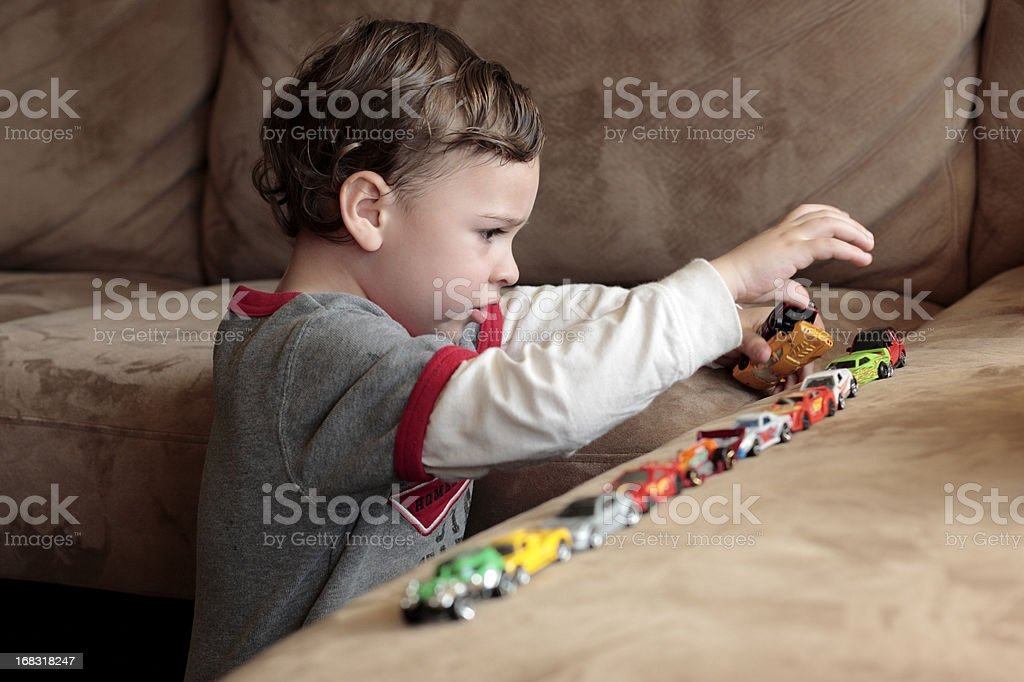 Autistic boy playing with toy cars stock photo
