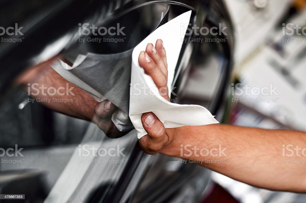 auto car worker and mechanic cleaning a cars window stock photo